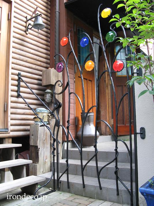 色が躍っているような背の高いロートアイアン門扉